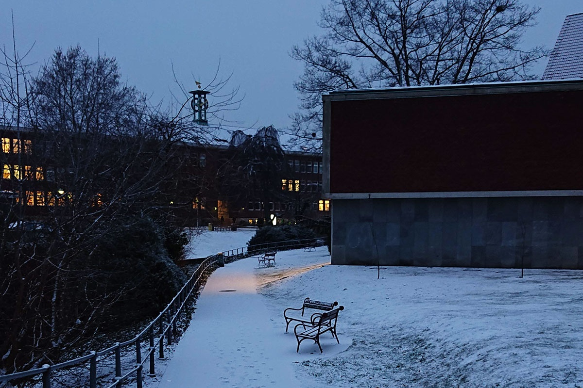 Schnee in Münster an der Aa mit Juridicum erleuchtet und roter Bank kurz vor der Petrikirche am Exzellenzcluster Religion und Politik