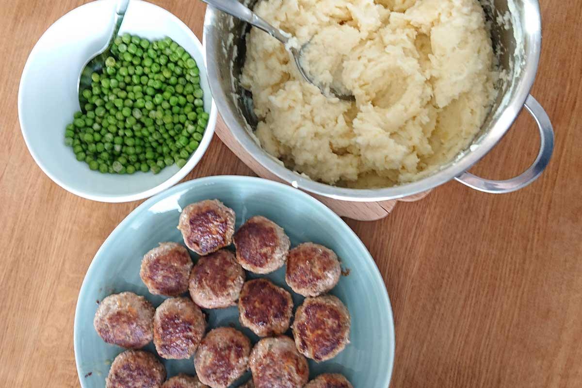 Mittagessen Klassiker Frikadellen Kartoffelpü und Erbsen