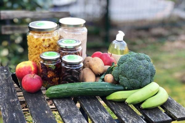 Lebensmittel Lieferung von Liefergrün in Gläsern und unverpackt Gurke Bananen Brokkoli Äpfel Kartoffeln Waschkonzentrat Nudeln und Mehl auf Gartentisch