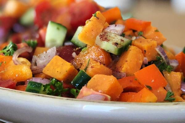 Süßkartoffelsalat in Nahaufnahme mit Gewürzen auf Süßkartoffelwürfel, Gurke, Tomate, Paprika auf einer braunen Keramikschale von Grün und Form