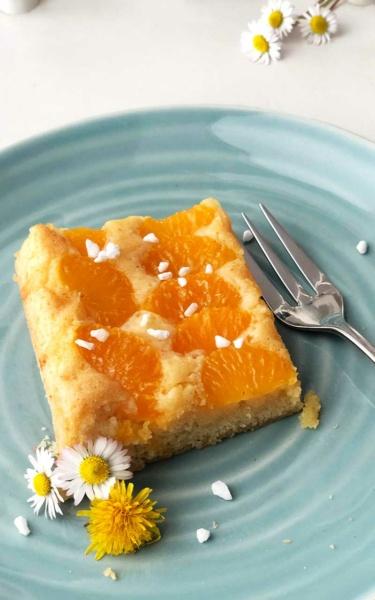 Mandarinenschnitte mit Gänseblümchen und Löwenzahn auf mintgrünem Teller auf weißem Holz Mandarinen Blechkuchen einfach rezept