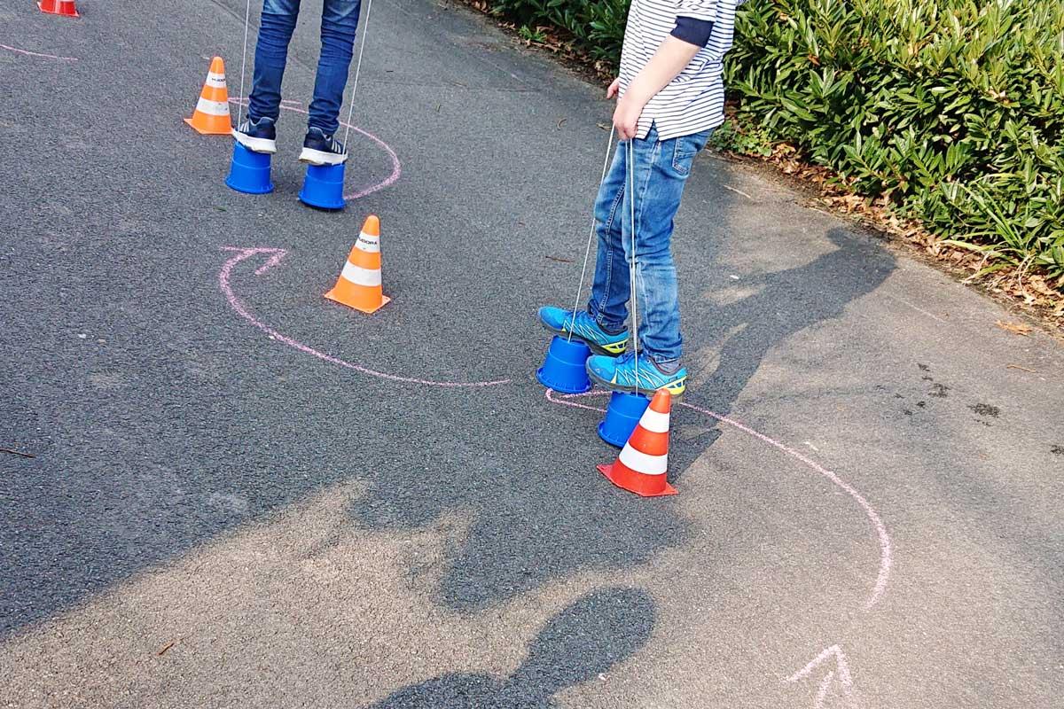 Kreativität als Lösungweg-Balance halten auf Stelzen Eimern Kinder machen es vor