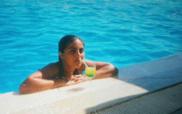 Mädchen mit Cocktail lehnt am Poolrand. Mit Selbstliebe älterwerden.